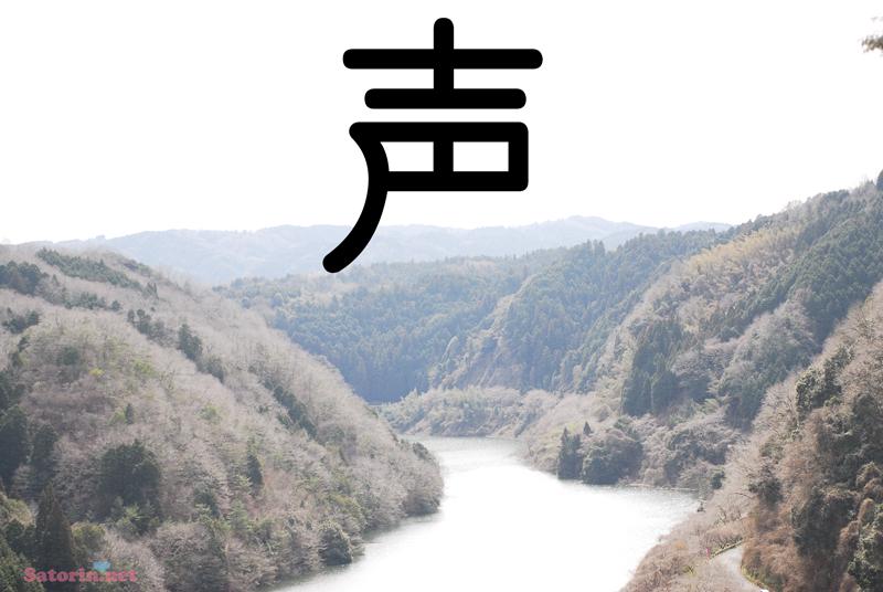 山に挟まれた川の写真に、大きく「声」と書かれている写真